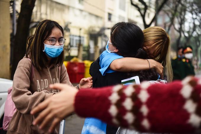 Hơn 300 người ở điểm cách ly tập trung Pháp Vân - Tứ Hiệp, Hà Nội, được về nhà nhà ngày 4/4. Sau hai tuần ở chung, các cô gái này trở nên thân thiết, ôm chặt lúc chia tay. Ảnh: Giang Huy.