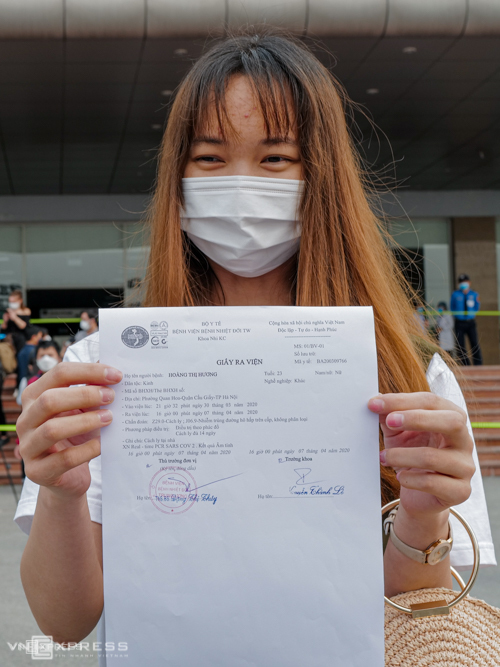 Cô gái vui mừng khoe giấy ra viện được Bệnh viện Bệnh Nhiệt đới Trung ương cấp, chiều 7/4. Ảnh: Ngọc Thành.