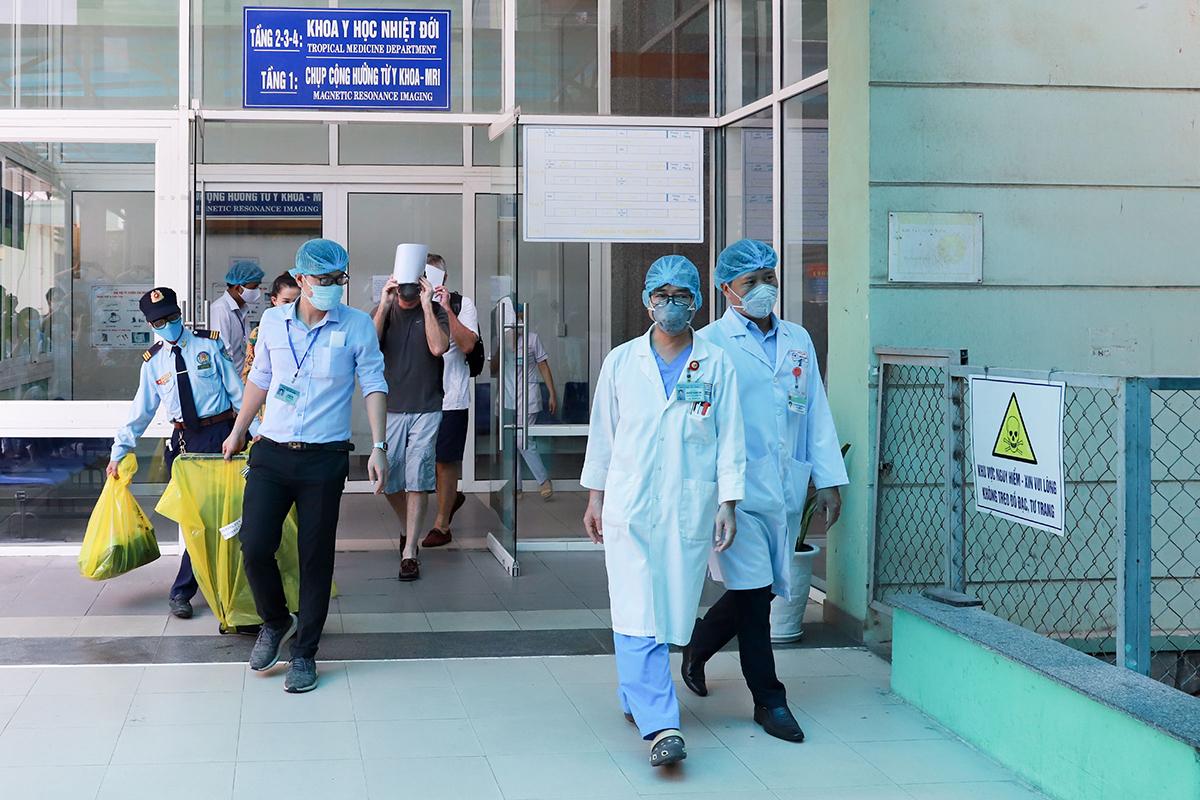 Hai du khách Anh - bệnh nhân 22 và 23 - dùng giấy che mặt, ra viện tại Đà Nẵng ngày 27/3. Ảnh: Nguyễn Đông.