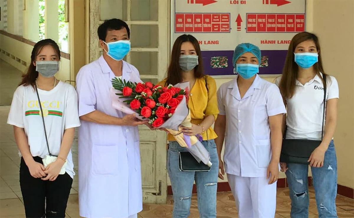Trang (ngoài cùng bên trái) và Thắm (ngoài cùng bên phải) cùng người thân tặng hoa cho đại diện bệnh viện. Ảnh: Gia Hân