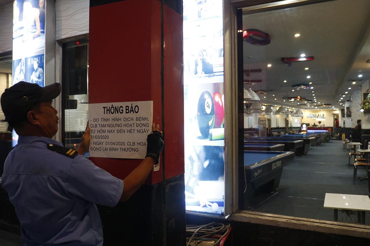 Nhân viên quán bida trên đường Nguyễn Kiệm, phường 9, quận Phú Nhuận, dán thông báo tạm ngưng hoạt động do dịch bệnh, chiều 24/3. Ảnh: Nguyệt Nhi.