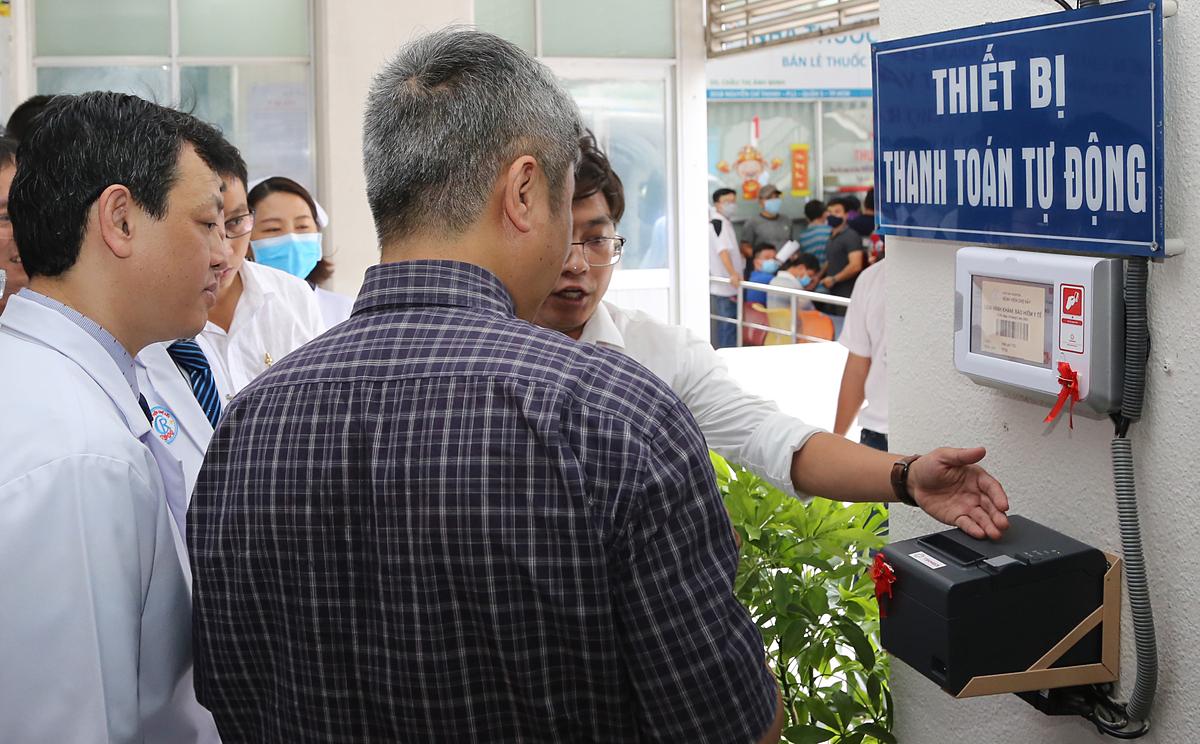 Nhân viên Bệnh viện Chợ Rẫy giới thiệu thẻ thanh toán tự động với Thứ trưởng Y tế Nguyễn Trường Sơn (áo sơ mi) chiều 18/5. Ảnh: N.H