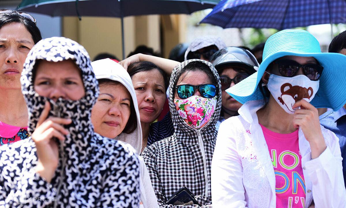 Người dân mặc áo dài, che ô chống nắng nóng. Ảnh:Giang Huy.