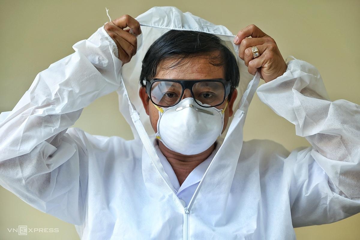 Bác sĩ Nguyễn Thanh Phong, Trưởng Khoa Nhiễm D, Bệnh viện Bệnh Nhiệt đới TP HCM chuẩn bị trang phục bảo hộ vào phòng chăm sóc bệnh nhân Covid-19. Ảnh: Hữu Khoa.