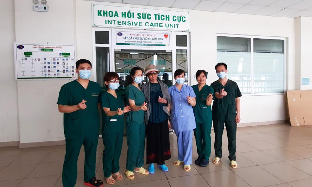 Bà Lê Tuyết Hằng (đeo kính) đứng chụp ảnh kỷ niệm cùng y bác sĩ tại bệnh viện sáng 3/6. Ảnh:Đặng Thanh.