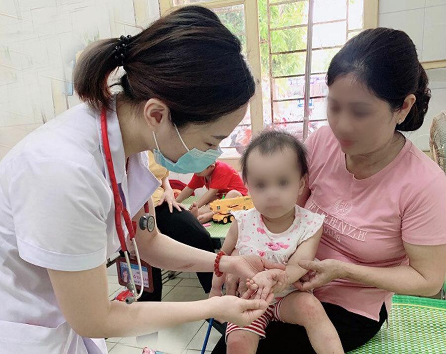 Bác sĩ khám cho bệnh nhi mắc tay chân miệng tại Bệnh viện Sản Nhi Nghệ An. Ảnh:Bệnh viện cung cấp.