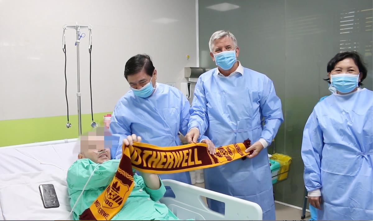 Bệnh nhân cùng lãnh đạo thành phố, Tổng Lãnh sự Anh và chiếc khăn Motherwell, tại Bệnh viện Chợ Rẫy chiều 17/6. Ảnh do bệnh viện cung cấp.