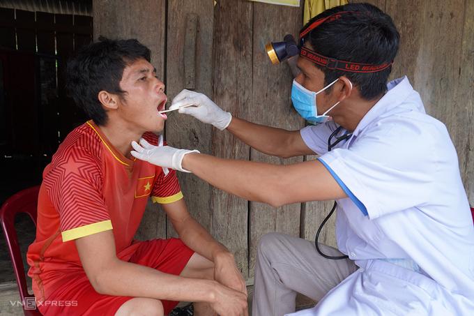 Trong khi GIàng A Phủ được chuyển về Bệnh viện Bệnh Nhiệt đới TP HCM, thì ở quê nhà Đăk Nông, anh trai của em (áo đỏ), 20 tuổi, được bác sĩ lấy mẫu bệnh phẩm xét nghiệm bạch hầu. Ảnh: Trần Hóa.