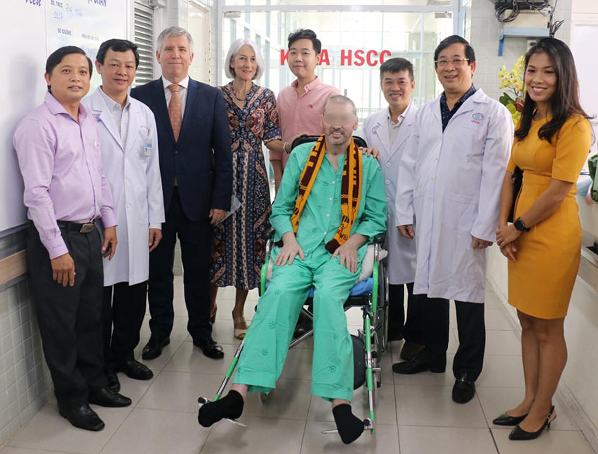 Bệnh nhân (áo xanh) chụp ảnh kỷ niệm với Cục trưởng Khám Chữa bệnh Lương Ngọc Khuê (thứ hai từ phải sang), các bác sĩ Bệnh viện Chợ Rẫy, đại diện Tổng Lãnh sự quán Anh, trước khi ra viện ngày 11/7. Ảnh do bệnh viện cung cấp.