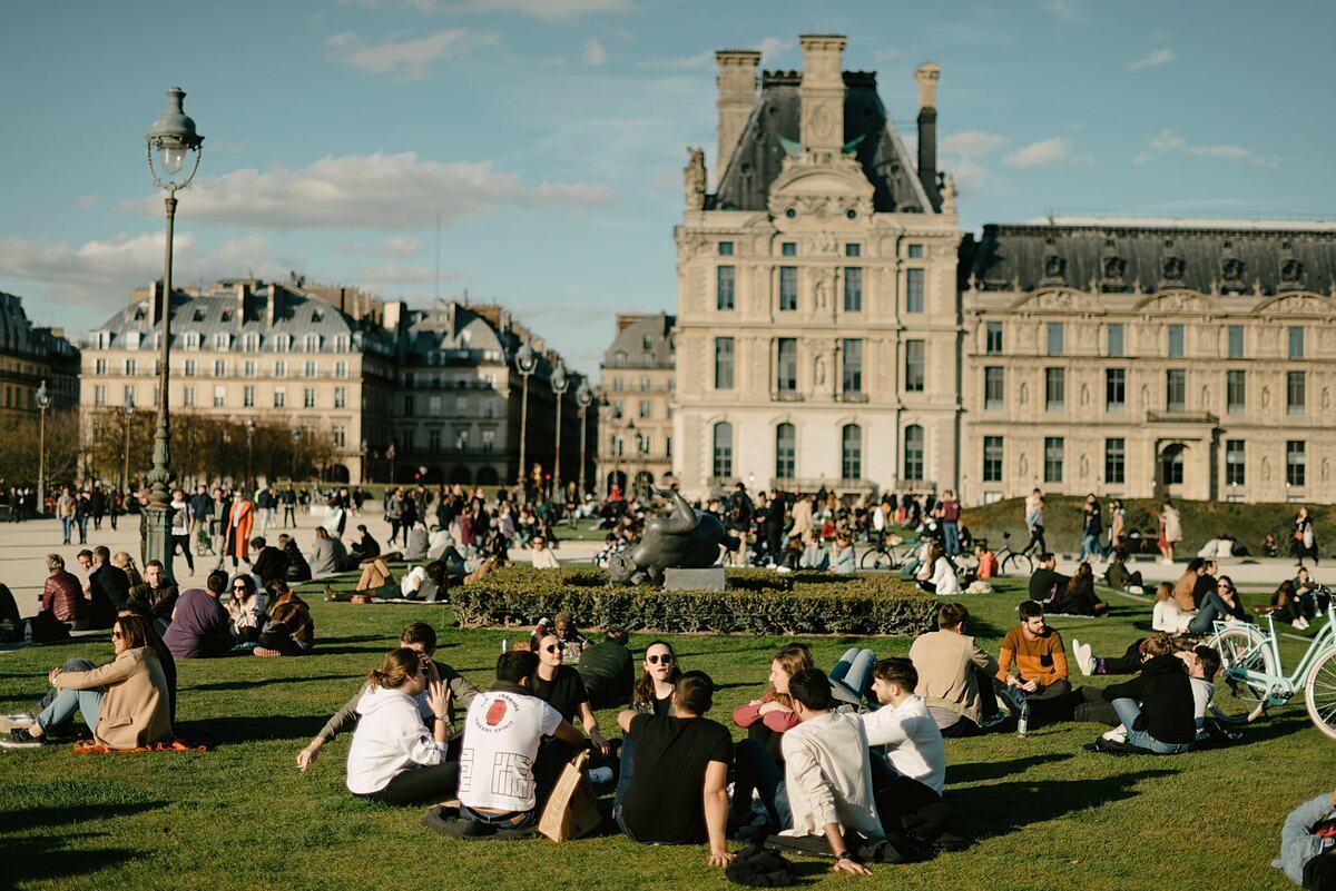 Người dân Paris thư giãn bên ngoài Bảo tàng Louvre, giữa tháng 3. Ảnh: NY Times