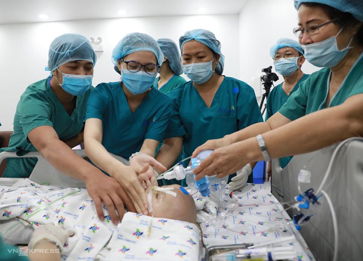Bé Diệu Nhi được các điều dưỡng chăm sóc sau khi kết thúc phẫu thuật chỉnh hình. Ảnh: Hữu Khoa.