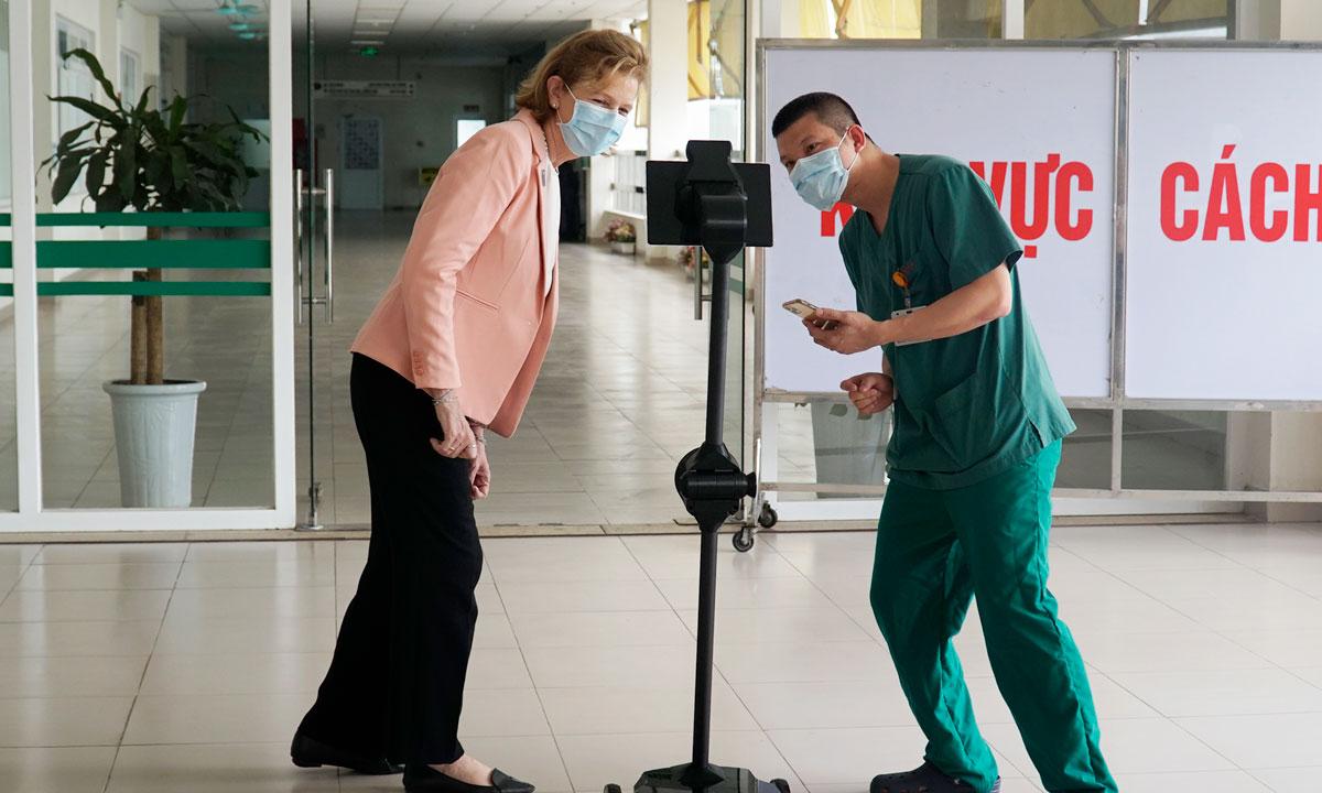 Bác sĩ Bắc (áo xanh) cùng bà Caitlin Wiesen, đại diện thường trú của UNDP tại Việt Nam, sử dụng robot Ohmni. Ảnh: Bệnh viện cung cấp.