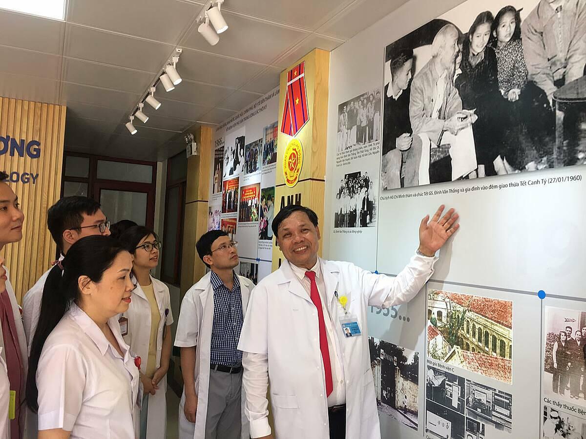 Ông Cường cùng các bác sĩ ôn lại lịch sử của bệnh viện qua triển lãm ảnh. Ảnh: Lê Nga.