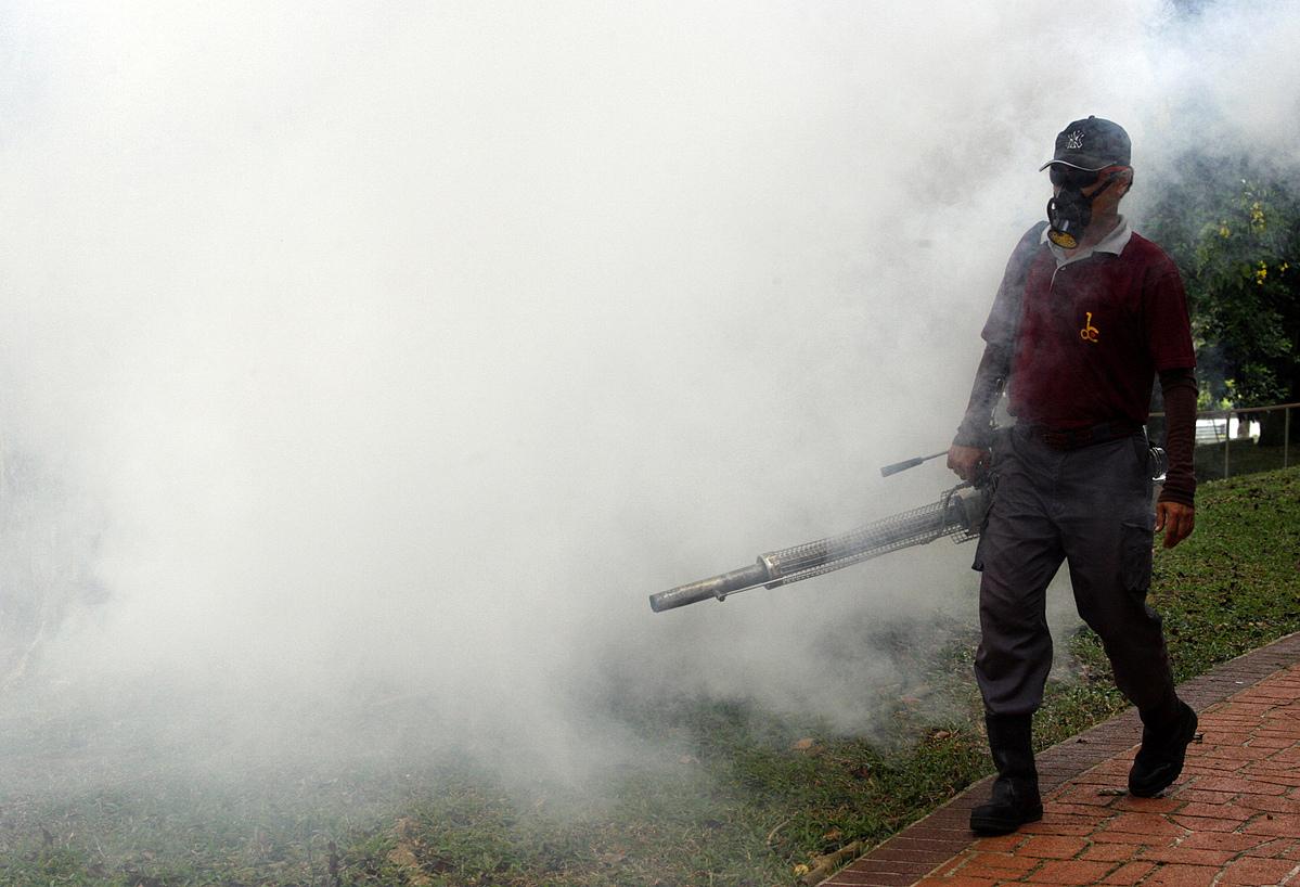 Nhân viên dịch vụ cộng đồng xịt thuốc chống muỗi tại một khu dân cư ở Singapore, ngày 13/7. Ảnh: Reuters
