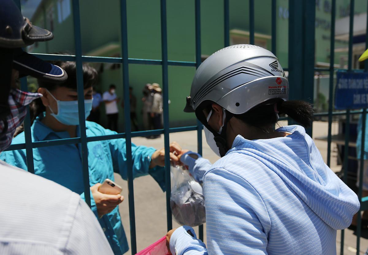 Người thân đưa đồ ăn cho bệnh nhân qua cổng sắt. Ảnh: Đắc Thành.