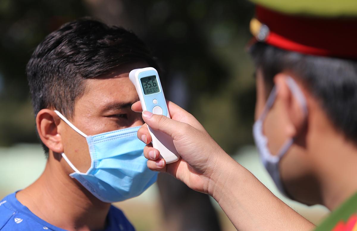 Cơ quan chức năng đo thân nhiệt người từ Đà Nẵng về Quảng Nam tại chốt kiểm dịch đường 603B, phường Điện Ngọc, thị xã Điện Bàn sáng 29/7. Ảnh: Đắc Thành.