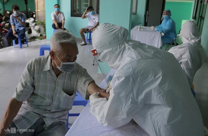 Nhân viên y tế phường Yên Hòa, quận Cầu Giấy lấy mẫu máu xét nghiệm cho người về từ Đà Nẵng ngày 30/7. Ảnh:Tất Định.