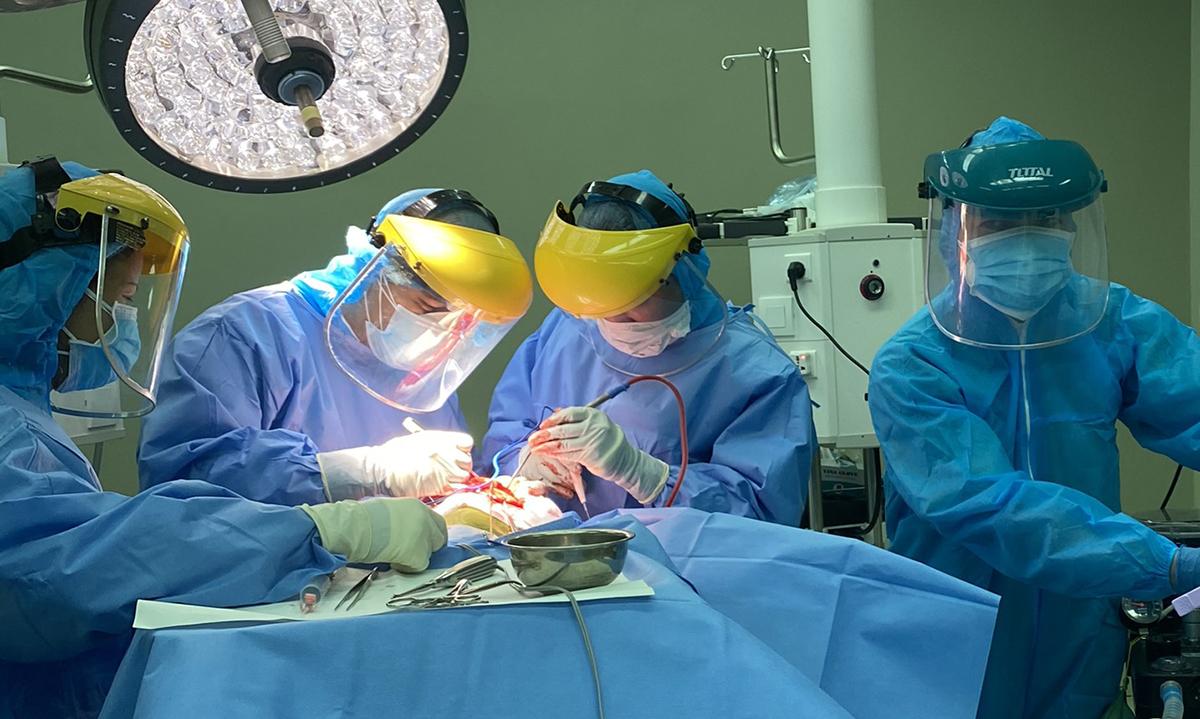 Bác sĩ Huy( thứ hai từ trái sang) cùng kíp trực trong trang phục bảo hộ tiến hành ca phẫu thuật chấn thương sọ não tối 31/7. Trung bình mỗi ngày từ một đến hai ca cấp cứu tại khoa. Ảnh: Bác sĩ cung cấp