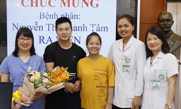 Bệnh nhân Tâm (áo vàng) cùng người nhà chụp ảnh kỷ niệm với đại diện bệnh viện. Ảnh: Thế Anh.