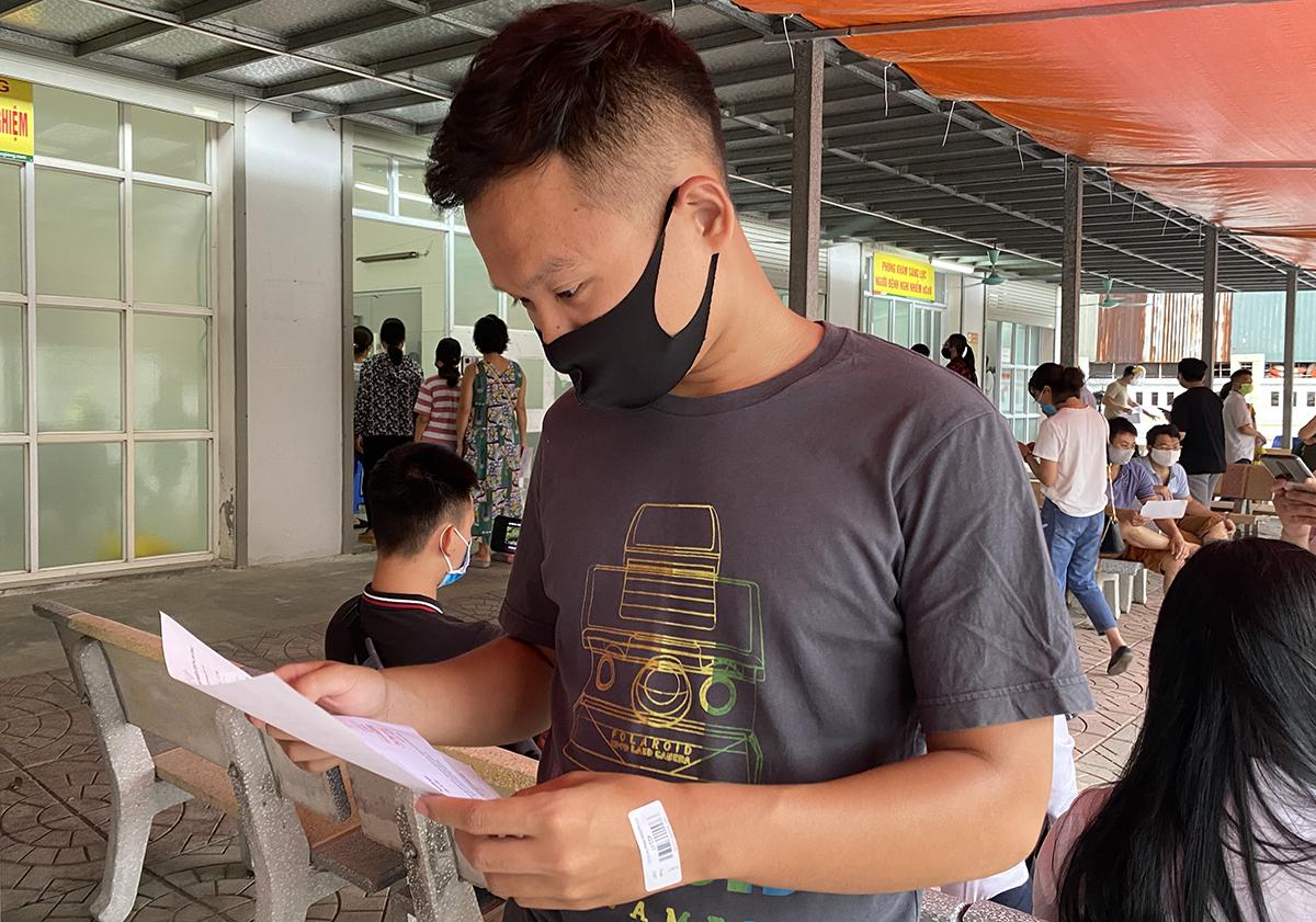 Anh Linh kiểm tra lại kết quả xét nghiệm sau khi khám sàng lọc tại bệnh viện Đa khoa Đức Giang ngày 31/7. Ảnh: Thùy An