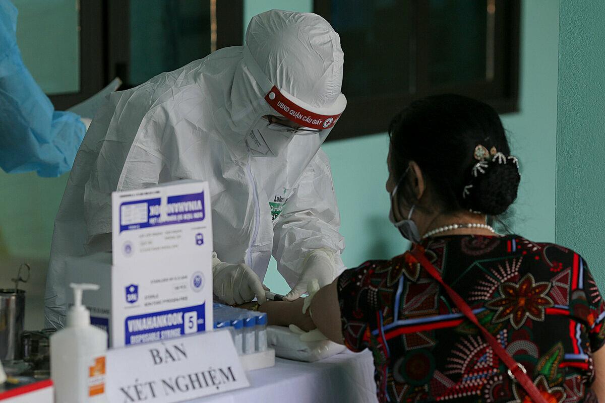 Nhân viên y tế phường Yên Hòa, quận Cầu Giấy, Hà Nội lấy mẫu máu xét nghiệm cho người về từ Đà Nẵng, ngày 30/7. Ảnh: Tất Định.