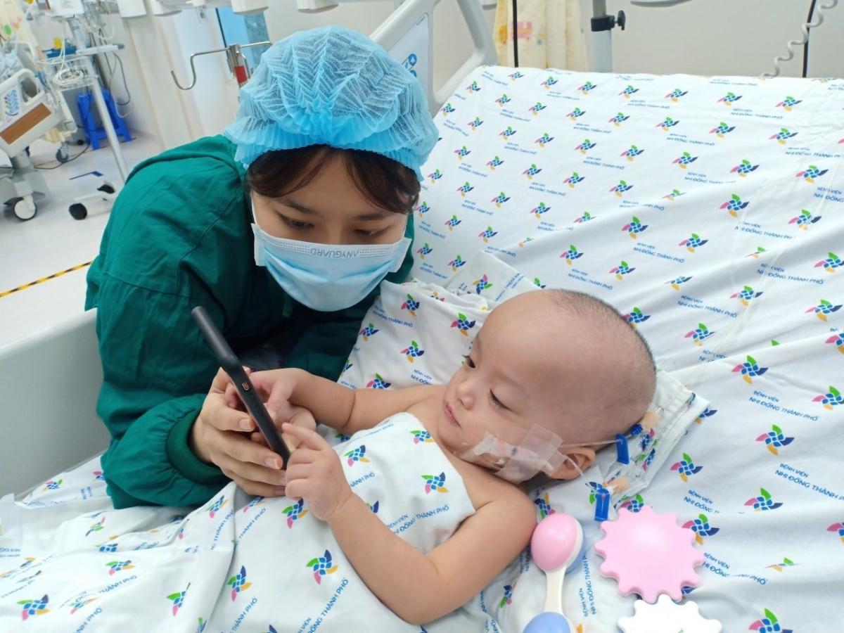 Trúc Nhi cử động linh hoạt các ngón tay khi điều dưỡng cho chơi điện thoại. Ảnh Nguyễn Lan Anh