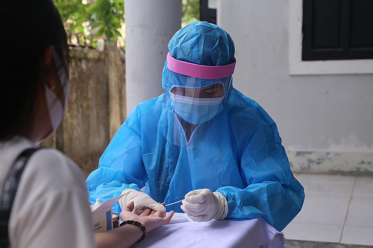 Lấy mẫu máu test nhanh Covid-19 cho người trở về từ vùng dịch ở TP Đông Hà, Quảng Trị, ngày 3/8. Ảnh:  Hoàng Táo.