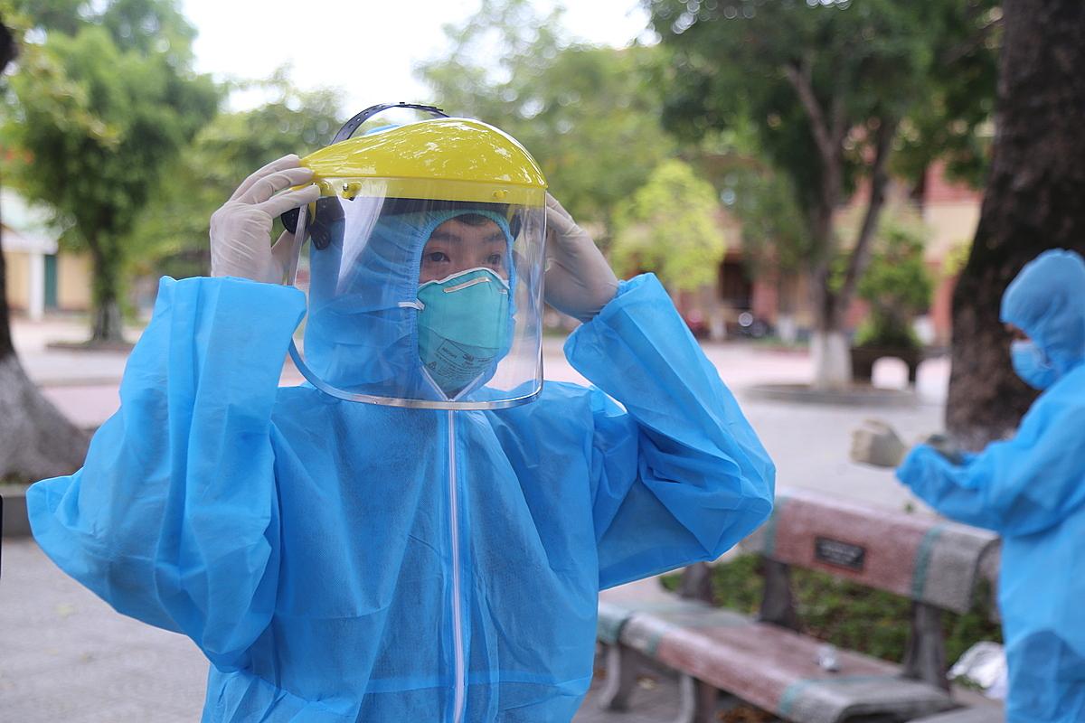 Nhân viên y tế Trung tâm y tế huyện Hải Lăng (Quảng Trị) mang trang phục bảo hộ trước khi lấy mẫu xét nghiệm nCoV. Ảnh: Hoàng Táo.
