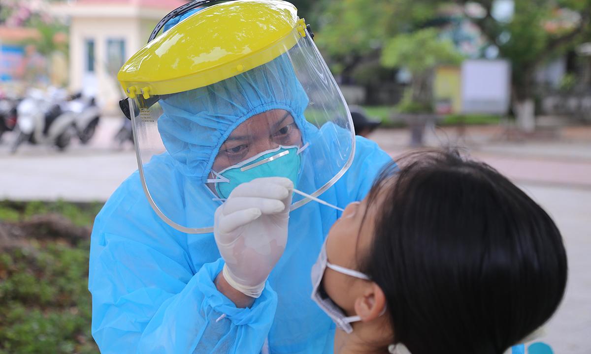 Nhân viên y tế Trung tâm y tế huyện Hải Lăng (Quảng Trj) lấy mẫu xét nghiệm Covid-19 cho học sinh lớp 12, do các em trở về từ vùng dịch Covid-19. Ảnh: Hoàng Táo