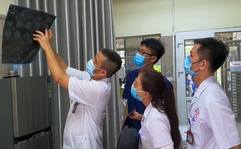 Bác sĩ Nguyên cùng đồng nghiệp kiểm tra phim chụp CT của bệnh nhân ngộ độc methanol. Ảnh: Mai Thanh.