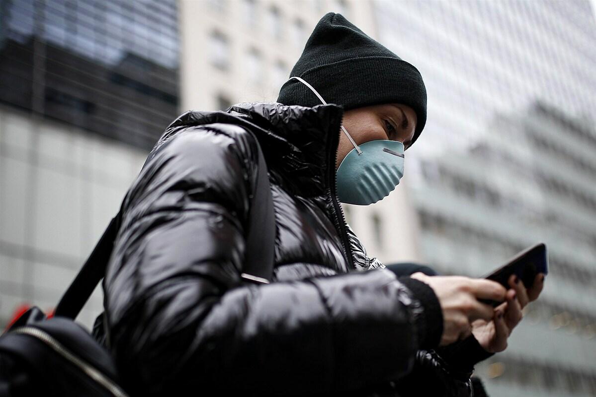 Một người dân tại New York đeo khẩu trang vào đọc tin tức trên đường phố, ngày 12/3. Ảnh: AP