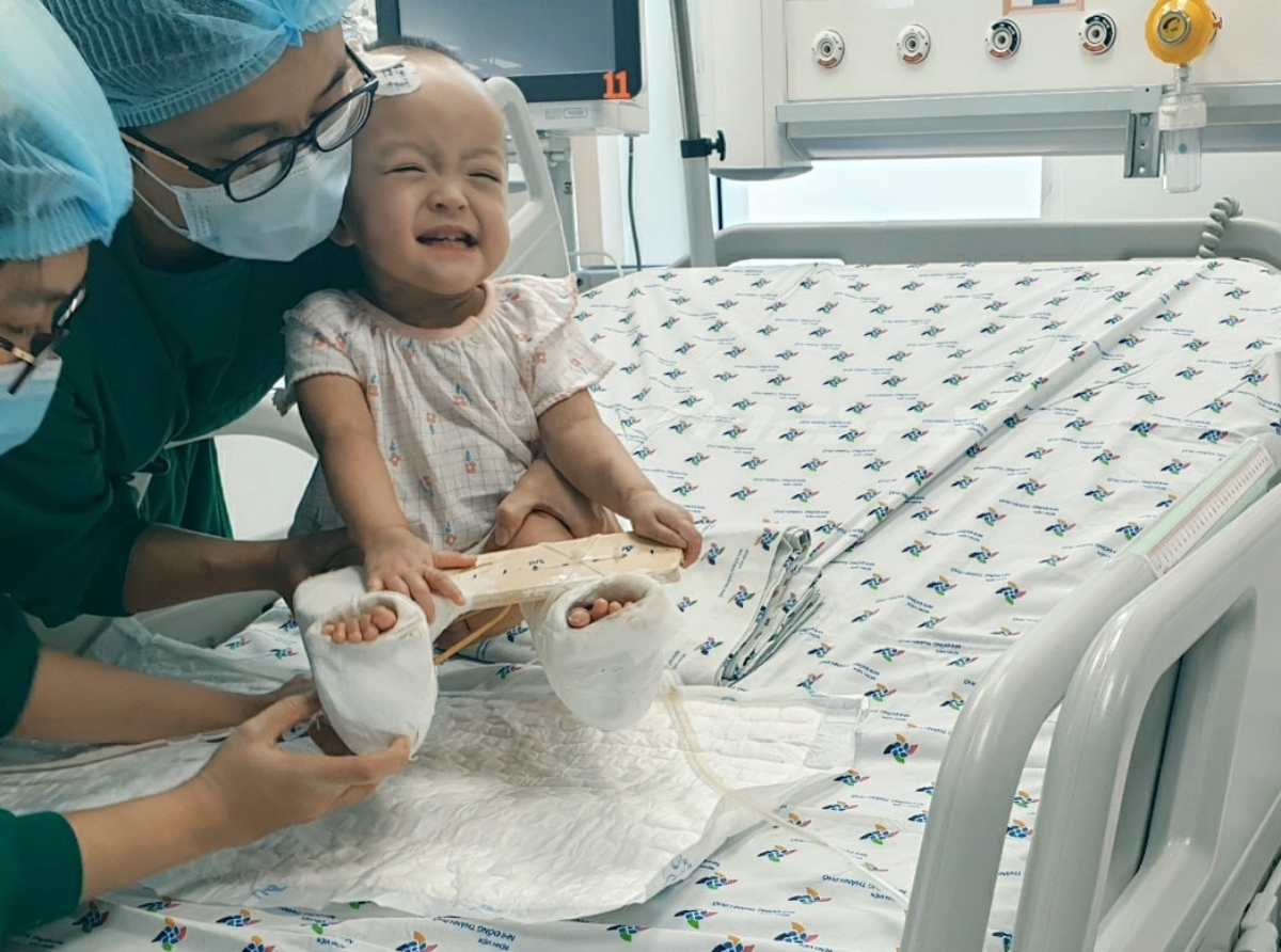 Bé Diệu Nhi cười típ mắt khi thấy chị gái mặc chiếc váy giống em, ngồi ngay ở giường bên cạnh chứ không xa như trước. Ảnh Bệnh viện cung cấp.