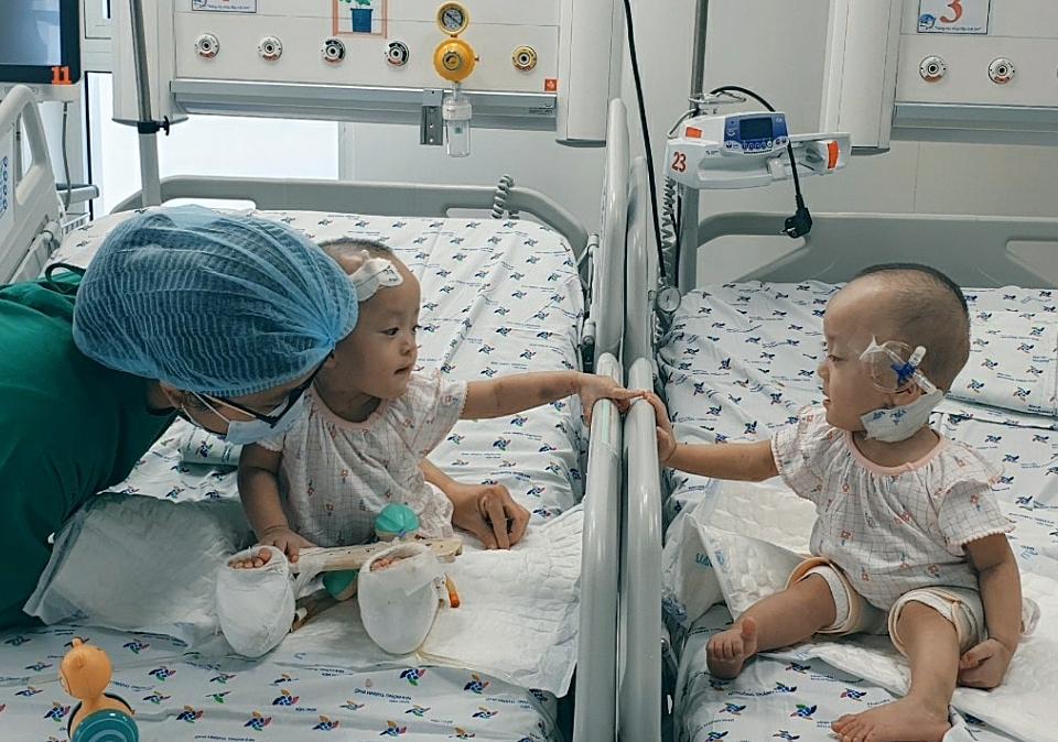 Vừa được gặp nhau, hai chị em đã sáp vào chạm tay, trò chuyện bằng ngôn ngữ riêng. Ảnh Bệnh viện cung cấp.