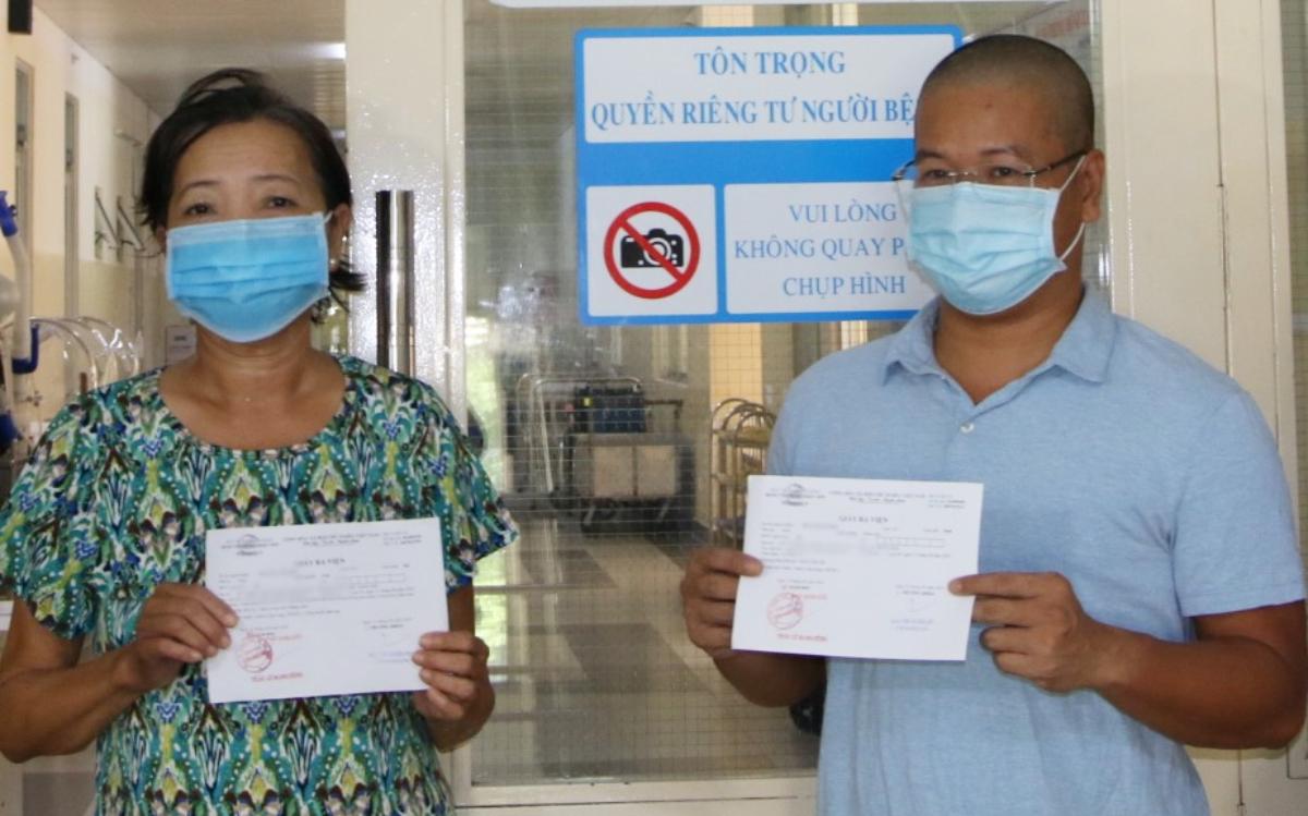 Bệnh nhân 517 và 589 nhận giấy ra viện và gửi lời cảm ơn các y bác sĩ đã tận tình chăm sóc họ những ngày điều trị Covid-19. Ảnh Thư Anh.