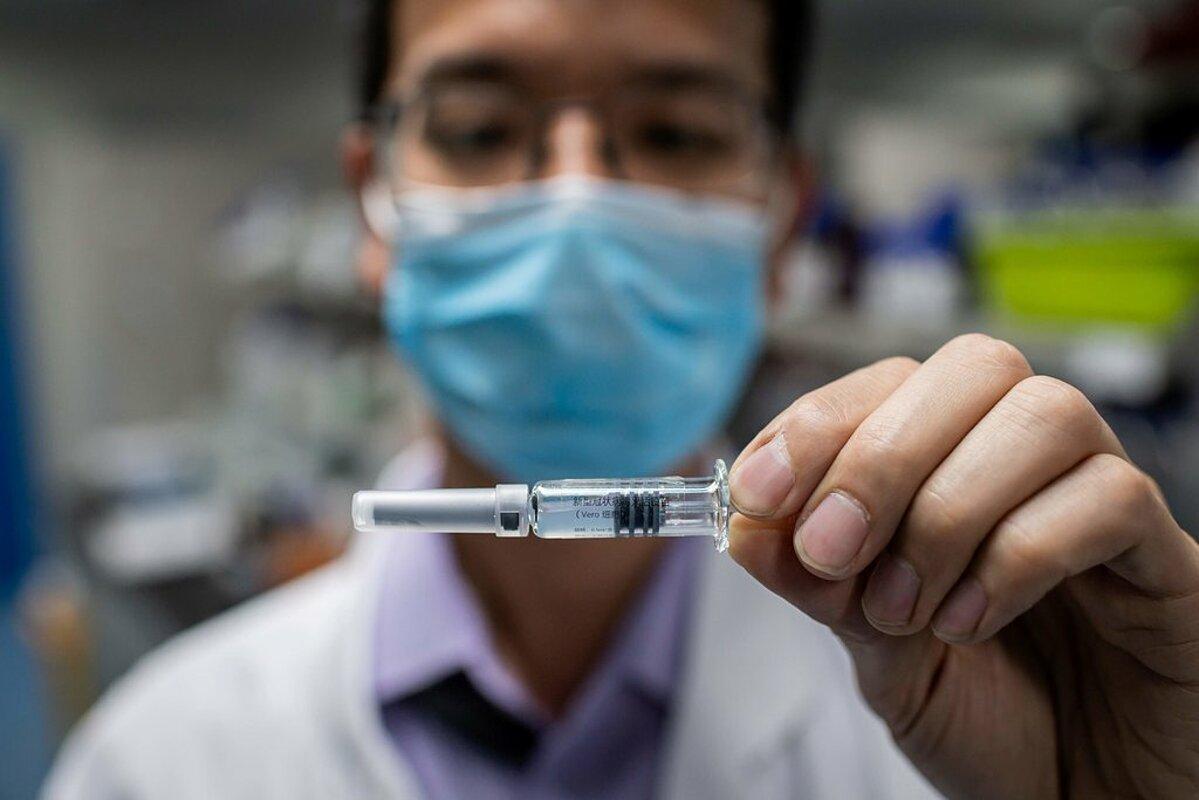 Nhà khoa học tại SinoVac cầm mẫu vaccine thử nghiệm hồi tháng 1 năm nay. Ảnh: AFP