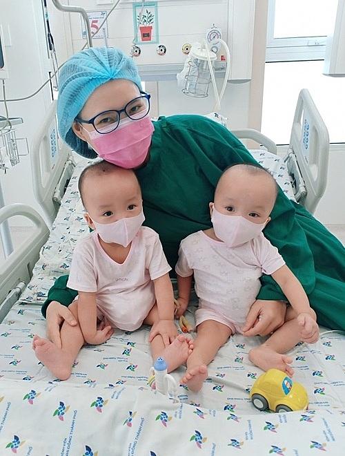 Hai bé chụp ảnh cùng mẹ trong lần đầu tập đeo khẩu trang. Ảnh: Bệnh viện cung cấp.