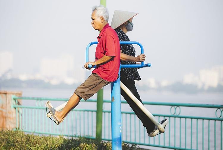Hai cụ ông, cụ bà ngoài 70 tuổi, tập thể dục ven hồ tây. Ảnh: Đình Tùng