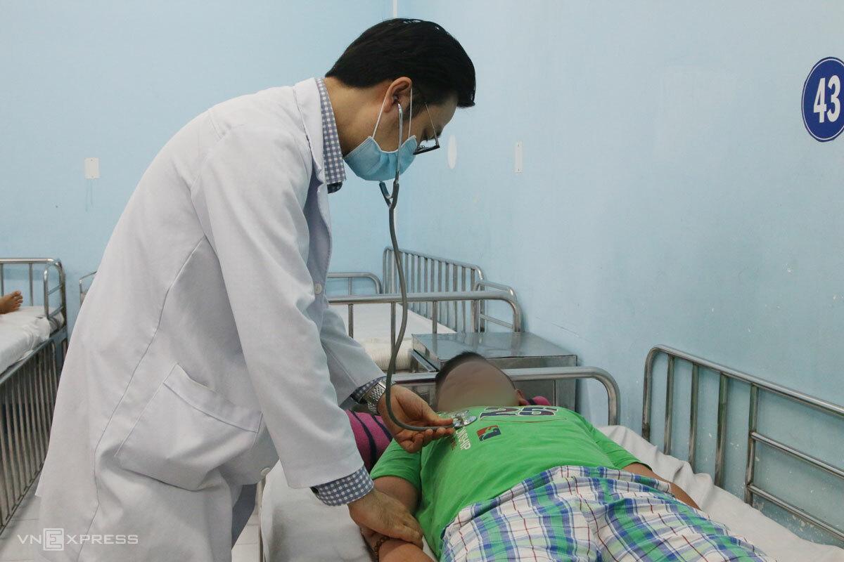 Bác sĩ Tuấn khám cho bệnh nhi mắc sốt xuất huyết. Ảnh: Thư Anh.