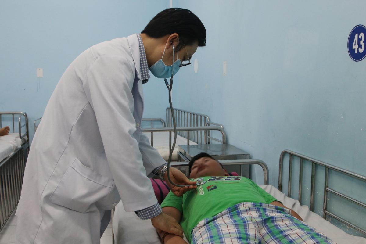 Bác sĩ Tuấn khám cho bệnh nhi sốt xuất huyết. Ảnh: Thư Anh