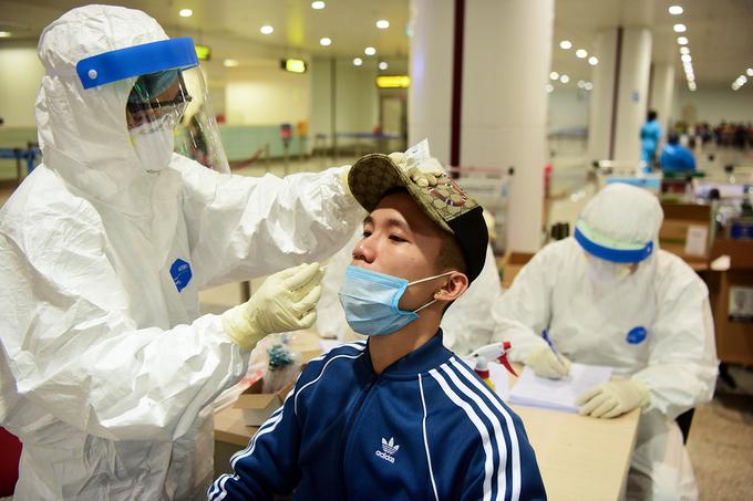 Cán bộ y tế lấy mẫu bệnh phẩm của từng người tại sân bay nội bài để xét nghiệm, hồi tháng 3. Ảnh:Giang Huy.