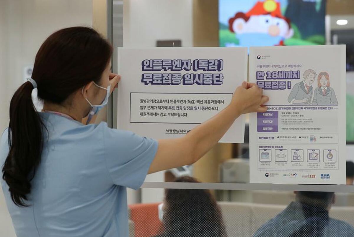Một nhân viên y tế dán thông báo tạm dừng tiêm phòng cúm ở bệnh viện tại Sejong, ngày 22/9. Ảnh: Reuters