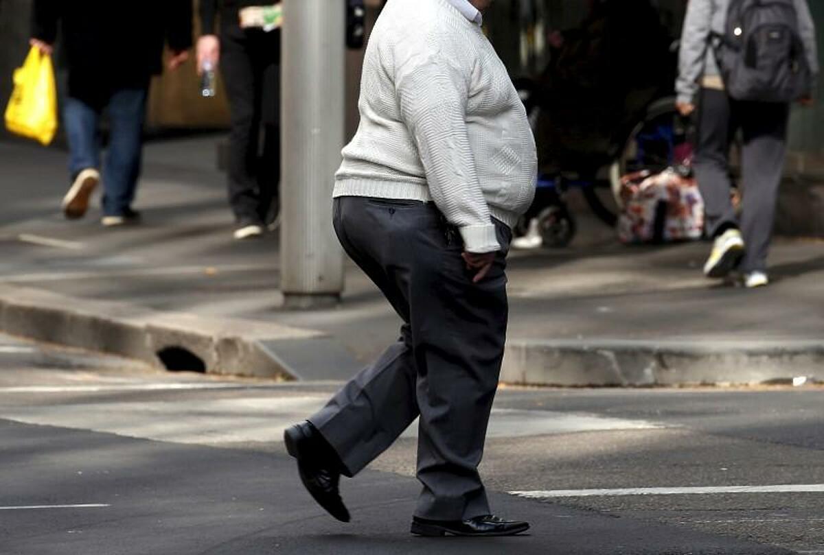 Một người đàn ông băng qua con đường tại Sydney. Ảnh: Reuters