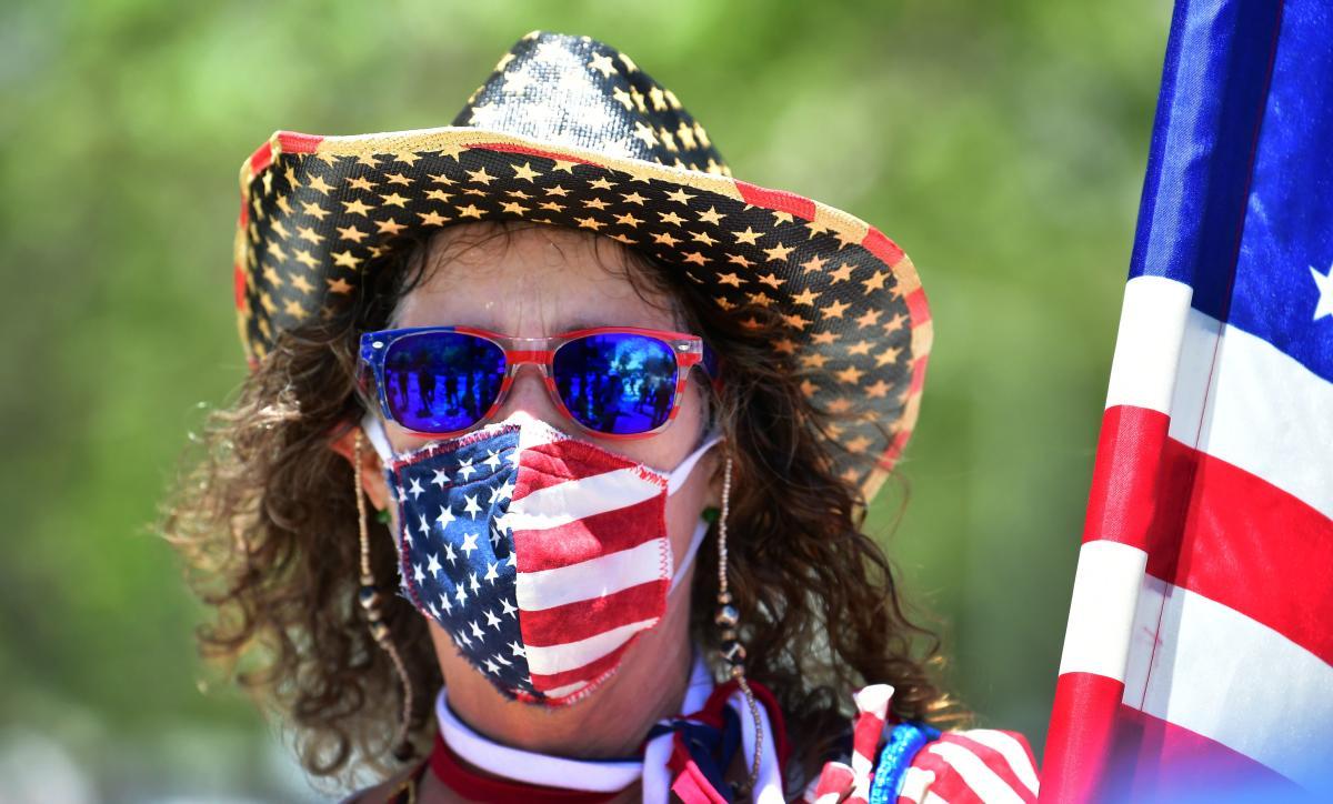 Người dân Mỹ đeo khẩu trang có hình quốc kỳ trong cuộc biểu tình kêu gọi thực hiện giãn cách xã hội. Ảnh: AFP