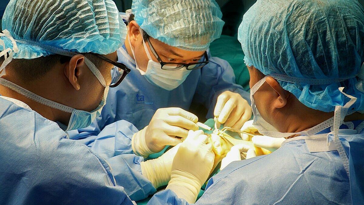 Phó giáo sư Trần Trung Dũng và êkip bác sĩ Trung tâm Phẫu thuật khớp - Y học thể thao bệnh viện Tâm Anh phẫu thuật thay đồng loạt 8 khớp ngón tay bị biến dạng cho bệnh nhân Trần Thị Ánh. Ảnh: Bệnh viện Tâm Anh cung cấp.