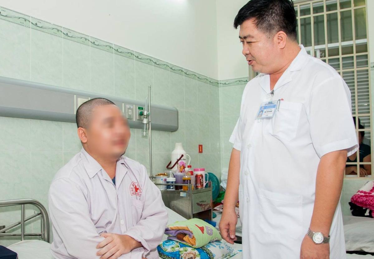 Đại tá bác sĩ Đào Tiến Mạnh, Giám đốc Trung tâm Chẩn đoán và Điều trị ung bướu, Bệnh viện Quân y 175 trò chuyện với một bệnh nhân ung thư. Ảnh: Lâm Hiếu.