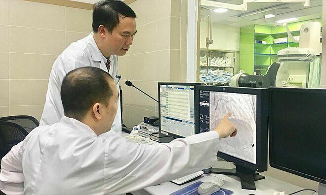 Phó giáo sư Hùng cùng đồng nghiệp chẩn đoán ca bệnh tim mạch. Ảnh: Lê Nga.