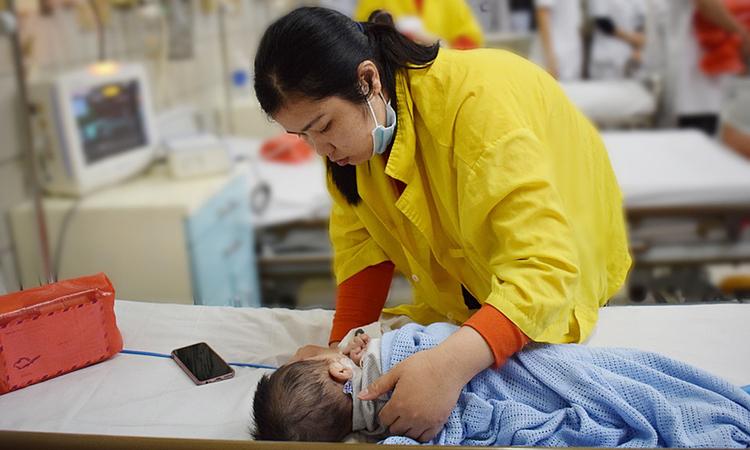 Người nhà chăm sóc bệnh nhi điều trị tại Bệnh viện Bạch Mai. Ảnh: Chi Lê.