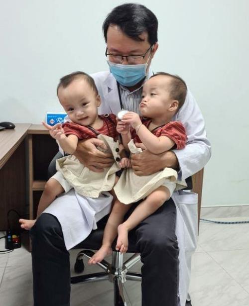 Trúc Nhi, Diệu Nhi tinh nghịch, làm mặt xấu khi ngồi trong lòng bác sĩ. Ảnh: Bệnh viện cung cấp.