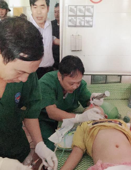 Các bác sĩ Bệnh viện Đa khoa huyện Cẩm Xuyên đặt nội khí quản cho bệnh nhi trưa 20/10. Ảnh: Hoàng Thúy Anh.
