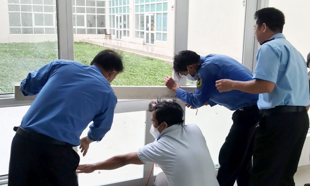 Nhân viên Bệnh viện Đa khoa Trung ương Quảng Nam gia cố cửa số bệnh viện để chống bão, sáng 28/10. Ảnh do bác sĩ cung cấp.